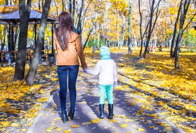 Punto di vista posteriore di giovane madre e sua figlia adorabile che camminano nella foresta gialla di autunno un giorno soleggiato caldo