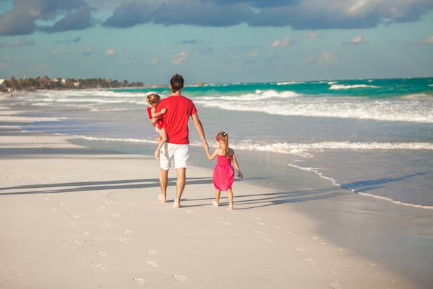 Punto di vista posteriore di giovane padre con le sue figlie sveglie che camminano lungo il mare