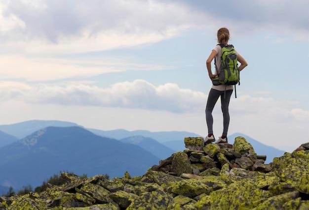 Punto di vista posteriore di giovane ragazza esile con gli zainhi che stanno sulla cima della montagna rocciosa contro il cielo blu luminoso di mattina che gode del panorama nebbioso della catena montuosa.