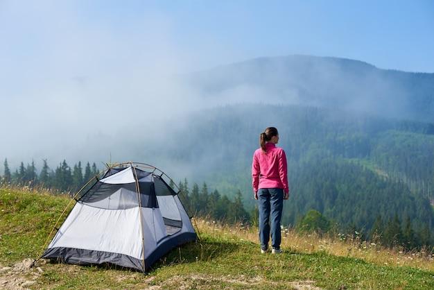 Punto di vista posteriore di giovane ragazza turistica dai capelli lunghi che sta sulla valle di fioritura alla tenda turistica sotto bello chiaro cielo blu che gode del mountain view sulla mattina luminosa di estate. turismo e concetto di viaggio.
