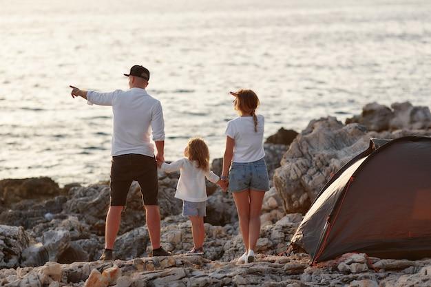 Punto di vista posteriore di giovani genitori felici, tenendosi per mano figlia, stante sulla spiaggia della roccia.