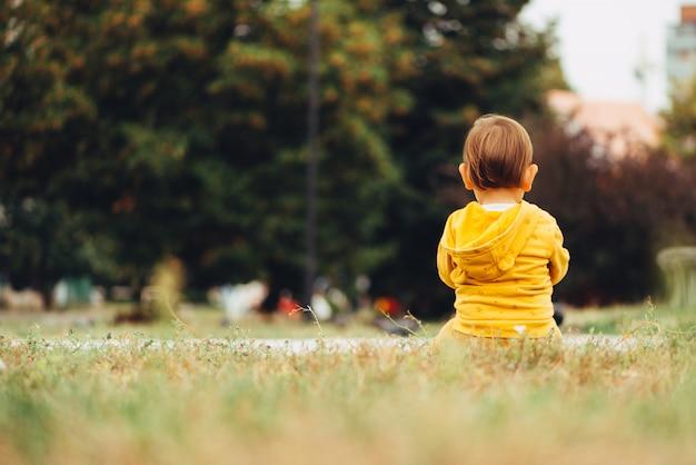 Punto di vista posteriore di piccolo neonato che si siede da solo all'aperto sull'erba. dof. copia spazio