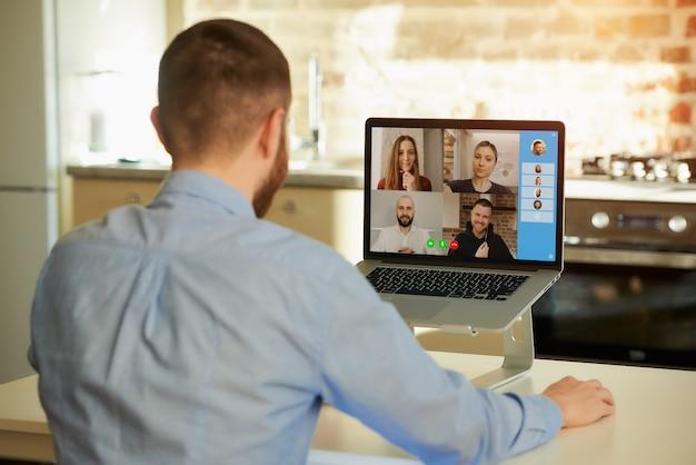 Punto di vista posteriore di un impiegato maschio che lavora a distanza ascoltando i suoi colleghi sull'affare in una videochiamata su un computer portatile a casa. un team multietnico in una riunione online.