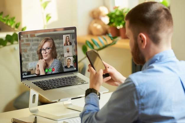 Punto di vista posteriore di un impiegato maschio che sta lavorando a distanza ascoltando i suoi colleghi in una videochiamata su un computer portatile e facendo affari su uno smartphone a casa.