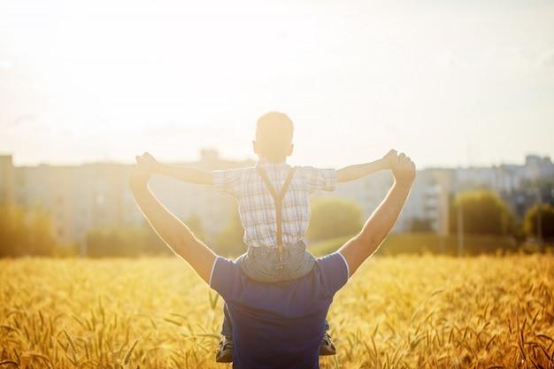 Punto di vista posteriore di un padre con suo figlio sulle spalle che stanno in un campo e città sul tramonto di estate