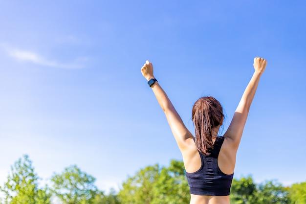 Punto di vista posteriore di una donna nell'allungare felicemente le sue braccia ad un campo all'aperto con gli alberi vaghi e chiaro cielo blu