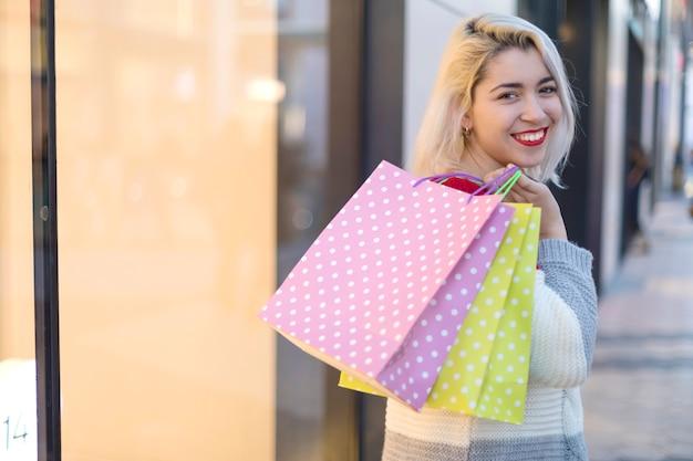 Punto di vista posteriore di una giovane donna sorridente che sta e che tiene le borse del negozio