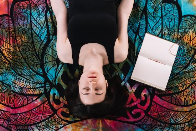 Punto di vista sopraelevato della donna chiusa degli occhi che si trova vicino al libro in bianco aperto sulla coperta