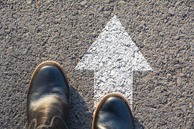Punto di vista superiore dell'uomo che indossa le scarpe nere che scelgono un modo segnato con le frecce bianche