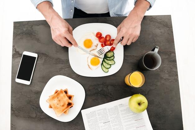 Punto di vista superiore dell'uomo che mangia prima colazione sana