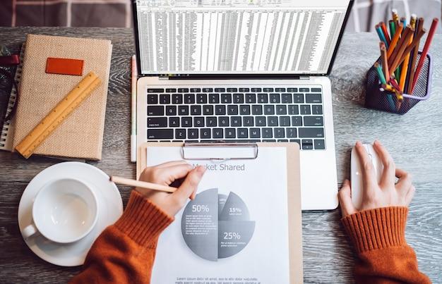 Punto di vista superiore della donna che lavora a casa facendo uso del computer portatile per analizzare la relazione di attività