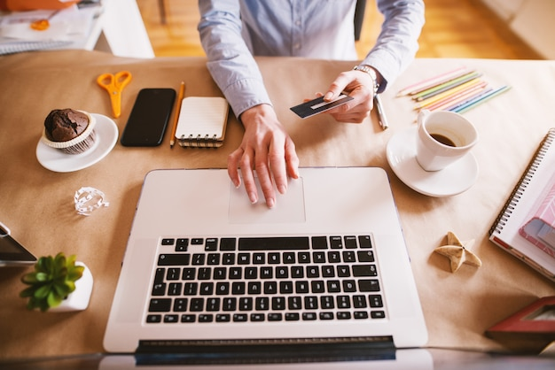 Punto di vista superiore della donna del progettista che compra online con la carta mentre sedendosi nel bello ufficio luminoso.