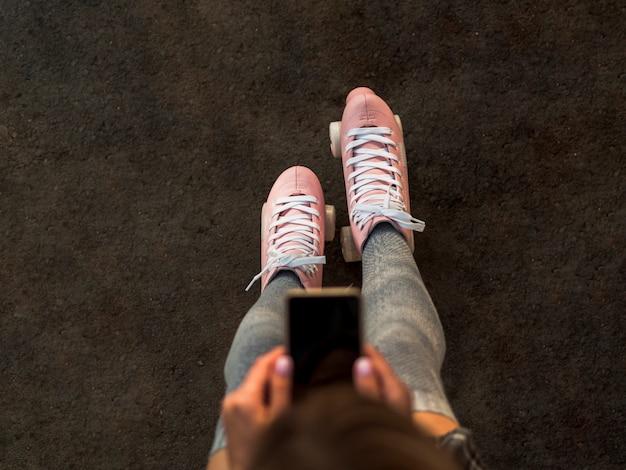 Punto di vista superiore della donna nei pattini di rullo che tengono smartphone