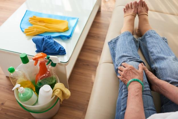 Punto di vista superiore della donna xropped seduta sul divano toccando il suo ginocchio doloroso sfinito dalla routine di pulizie