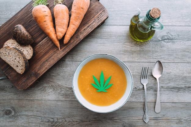 Punto di vista superiore della giovane donna che mangia la minestra di carota con l'olio e la foglia di marijuana dentro