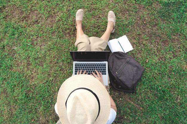 Punto di vista superiore della giovane donna che utilizza computer portatile mentre sedendosi nel giardino.