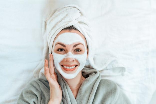 Punto di vista superiore della giovane donna sorridente con la maschera facciale che si riposa e che esamina macchina fotografica.
