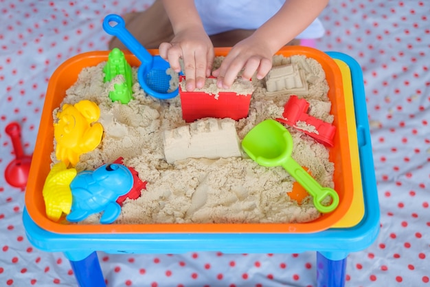 Punto di vista superiore vicino su di piccolo bambino asiatico di anni del ragazzo che gioca con la sabbia cinetica a casa
