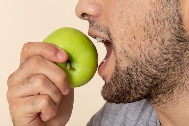 Punto di vista vicino frontale del giovane in maglietta grigia e blue jeans che morde mela verde