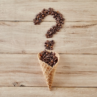 Punto interrogativo del chicco di caffè dal cono della cialda