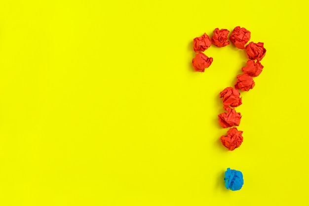 Punto interrogativo rivestito con carta stropicciata su spazio giallo copia vista dall'alto