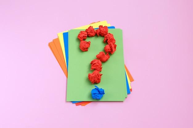 Punto interrogativo rivestito con carta stropicciata sullo spazio colorato copia vista dall'alto