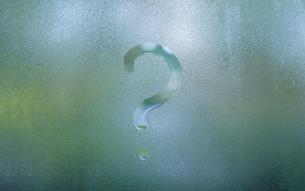 Punto interrogativo sfocato sul vetro della finestra di condensa nebbiosa