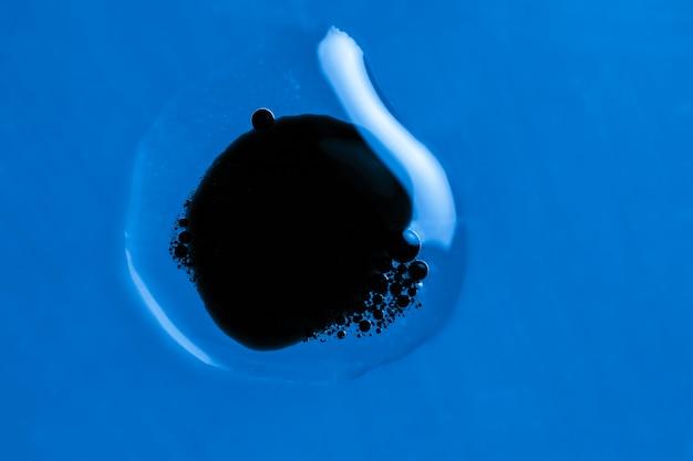Punto nero in una goccia d'acqua sfondo blu