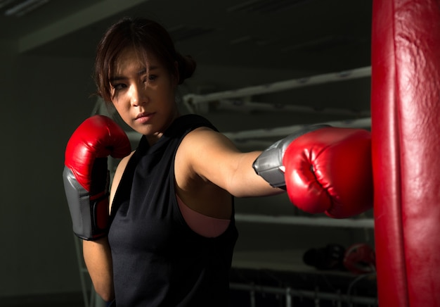 Punzone femminile del pugile all'obiettivo in palestra, sport di pugilato
