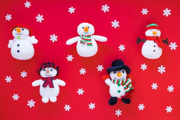 Pupazzi di neve divertenti del giocattolo fra i fiocchi di neve dell'ornamento