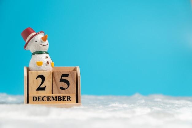 Pupazzo di neve che indossa un cappello rosso seduto sul calendario di blocchi di legno impostato per la data di natale 25 de
