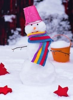 Pupazzo di neve con un secchio in testa sulla neve bianca