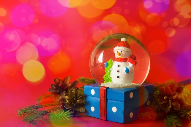 Pupazzo di neve del globo della neve del nuovo anno e di natale dentro sul fondo rosso del bokeh