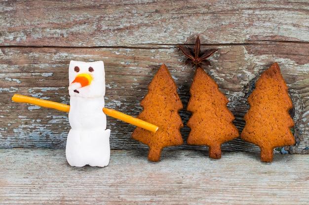 Pupazzo di neve e pan di zenzero divertenti della caramella gommosa e molle di concetto del buon anno su fondo di legno