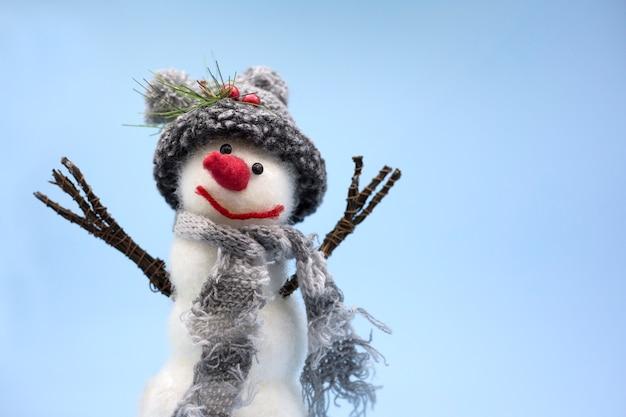 Pupazzo di neve giocattolo su uno sfondo blu con cappello a maglia grigia e sciarpa grigia