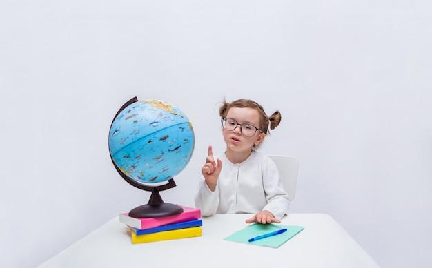 Pupilla ragazza intelligente attira l'attenzione sedendosi a un tavolo con un globo e libri su un bianco isolato