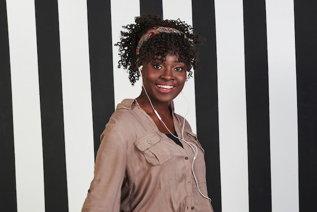 Pura felicità. la ragazza afroamericana sorrisa sta nello studio con le linee bianche e nere verticali a fondo