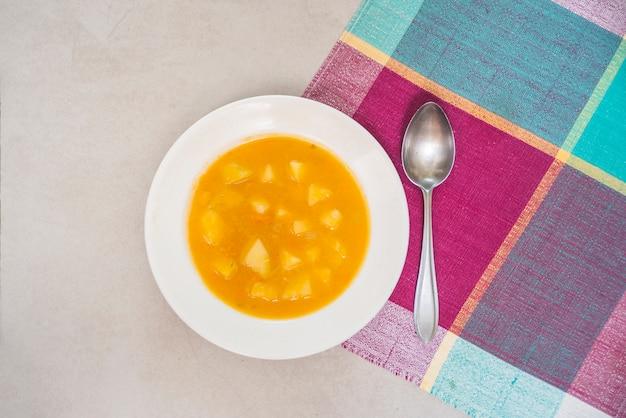 Purea di zucca e cucchiaio sul ripiano del tavolo