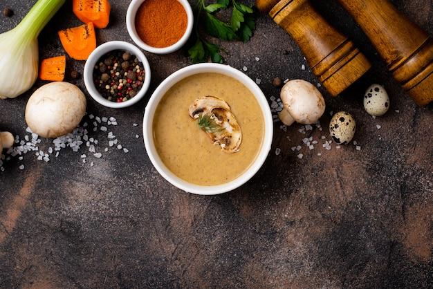 Purea di zuppa di funghi in un piatto con spezie e requisiti di cucina su un tavolo nero