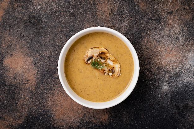 Purea di zuppa di funghi in un piatto su un tavolo nero.
