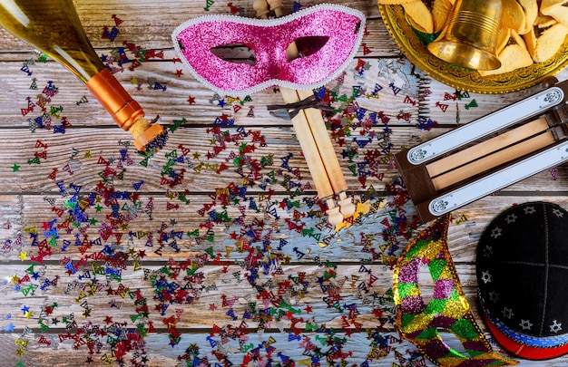 Purim tradizionale con biscotti hamantaschen, noisemaker e maschera di carnevale su fondo di legno
