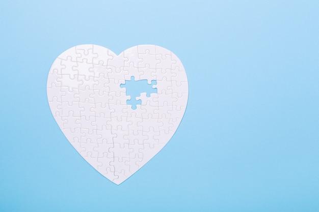 Puzzle bianco a forma di cuore sul blu