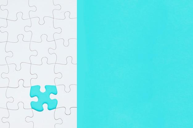 Puzzle bianco con pezzo mancante su sfondo turchese