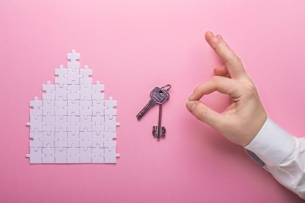 Puzzle bianco puzzle di forma della casa. il concetto di affitto, mutuo. mani che tengono le chiavi vista dall'alto