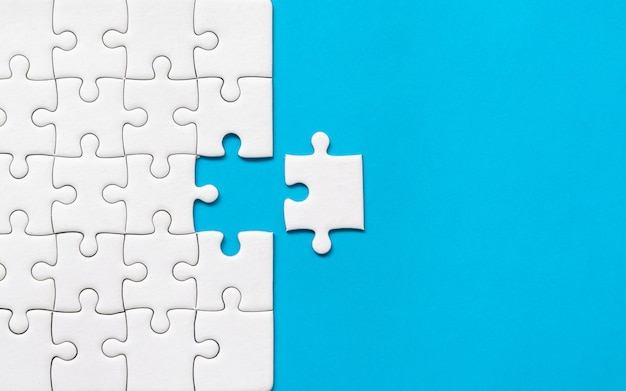 Puzzle bianco su sfondo blu. collaborazione o lavoro di squadra successo aziendale.