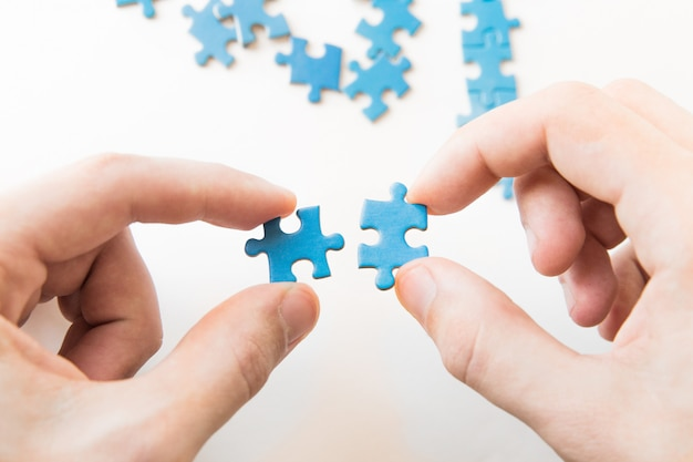 Puzzle blu in mano. pezzo di puzzle della tenuta della mano su fondo bianco. collegamento di un pezzo di puzzle, relazione d'affari, istruzione, società e lavoro di squadra