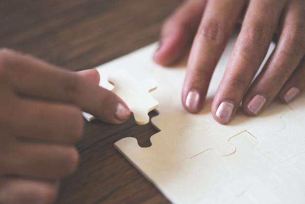Puzzle con il pezzo di collegamento del puzzle della mano della donna su legno / successo e strategia di associazione delle soluzioni di affari