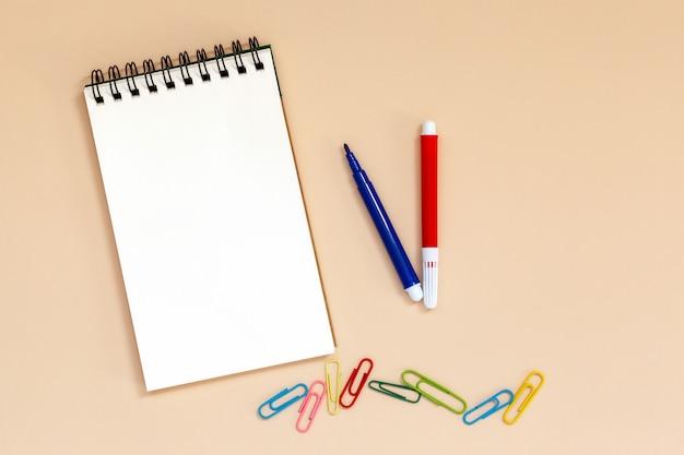 Quaderno a spirale bianco con penne colorate e clip sul tavolo.
