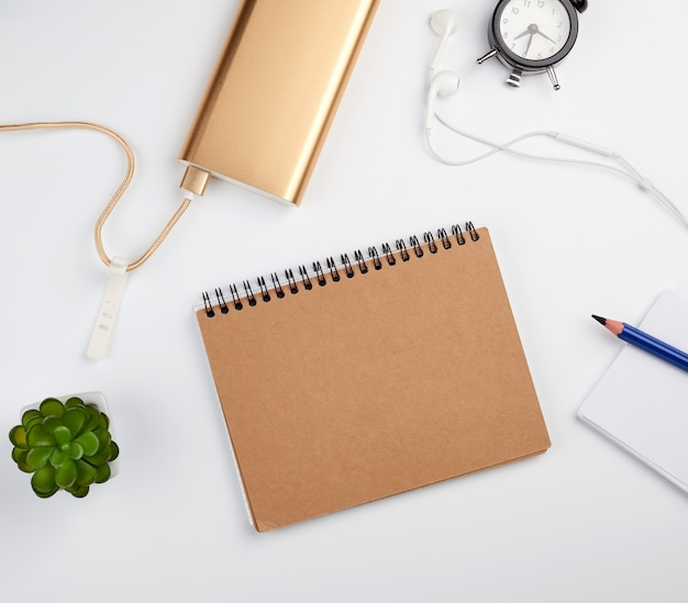 Quaderno a spirale con fogli vuoti, penna e piante verdi