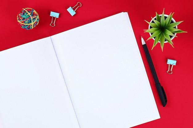 Quaderno bianco su sfondo rosso